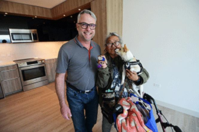 Patricia Hayashi, with her dog, Snow, shows the keys to<br>her new apartment as Q Foundation&#039;s Brian Basinger looks on. Photo: Rick<br>Gerharter
