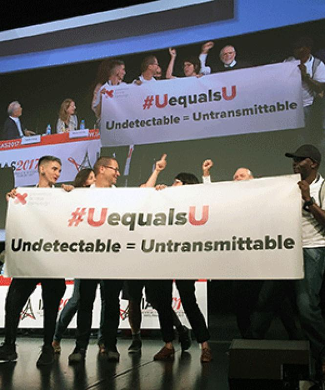 AIDS advocates unfurled a banner during the plenary<br>session on the final day of the International AIDS Society Conference in Paris.<br>Photo: Liz Highleyman