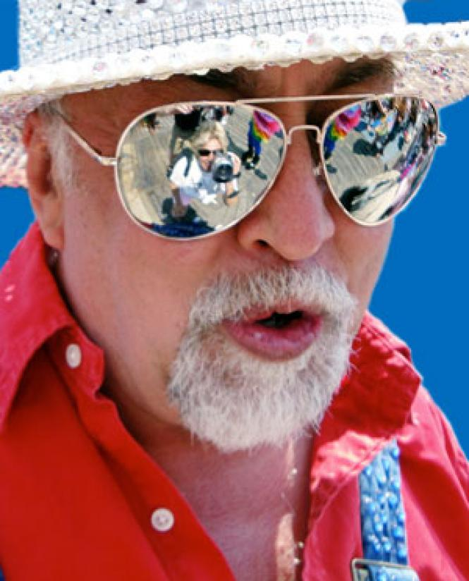 Rainbow flags are reflected in Gilbert Baker's sunglasses<br>in this photo from 2010. (Photo: Charley Beal)