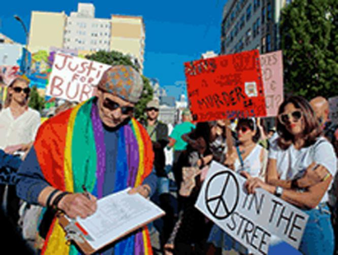 """A man signs a petition asking city officials to take action in the case of Anthony """"Bubbles"""" Torres, who was fatally shot in the Tenderloin September 9"""