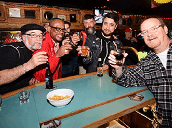 Bartender Matt Wruble (right) at the Gangway Bar toasts the community with a group of patrons in January 2016