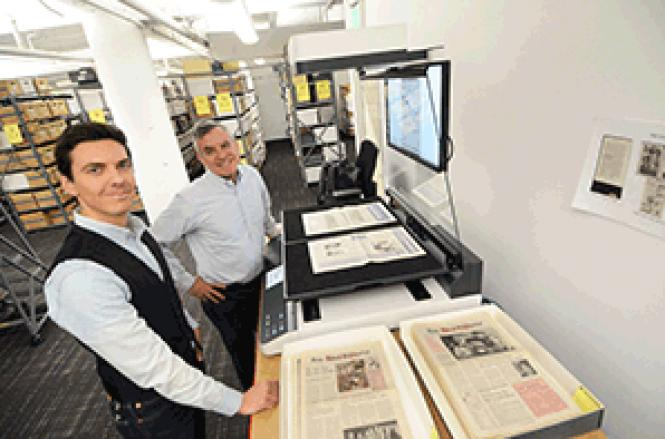 Bill Levay (left), digitization project archivist at the GLBT Historical Society, and Executive Director Terry Beswick demonstrate how the scanning process works to make old copies of the Bay Area Reporter accessible online
