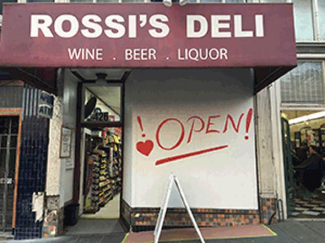 A boarded up window at Rossi's Deli signals to customers Tuesday that the shop is open after a man driving a van allegedly hit the building Saturday.