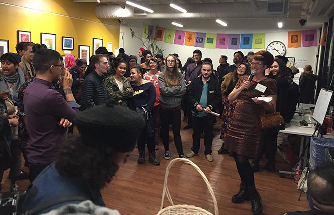 Katie Gilmartin, holding microphone, welcomes artists and visitors to the Queer Ancestors Project exhibit opening last month at Strut.