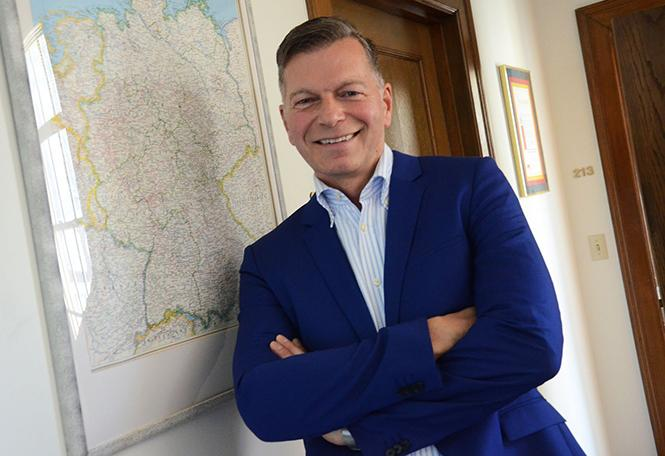 German Consul General Hans-Ulrich Suedbeck stands beside a map of Germany. Photo: Rick Gerharter