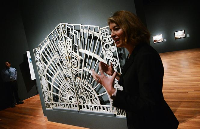 Emma Acker, Associate Curator at the de Young Museum, speaks about the gate designed by Rene Paul Chambellan and used for the entrance to the executive suite in New York's Art Deco Chanin Building. Photo: Rick Gerharter