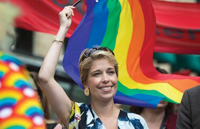 Swedish Minister for Social Affairs Annika Strandhäll waves a rainbow flag at a Pride parade. Photo: Courtesy of TT/The Local Sweden