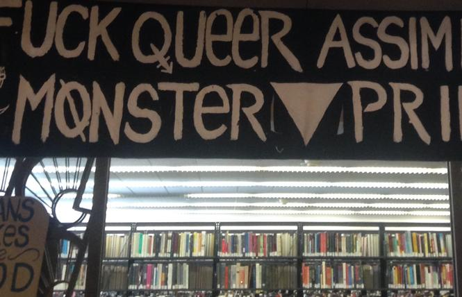 "A Pride banner and two ""Trans Dykes Are Good and Pure"" shields are part of the ""Degenderettes Antifa Art"" exhibition at the San Francisco Public Library's main branch. Photo: Christina A. DiEdoardo"