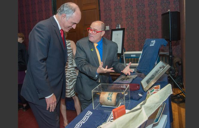Pennsylvania Senator Bob Casey, left, listens to Philadelphia Gay News publisher Mark Segal explain some of the items he donated to the National Museum of American History. At lower left is an old Bay Area Reporter T-shirt. Photo: Patsy Lynch