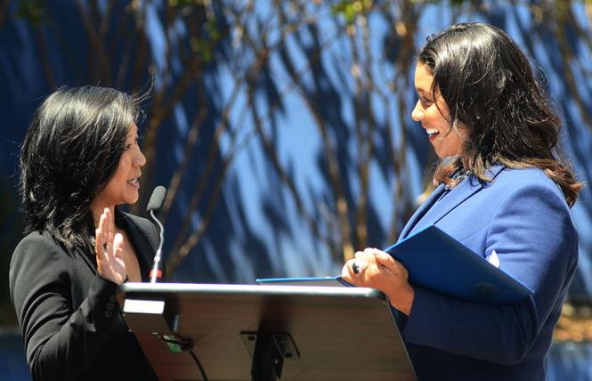 vy Lee, left, is sworn in by Mayor London Breed as the newest member of the City College of San Francisco Board of Trustees July 20. Photo: Rick Gerharter