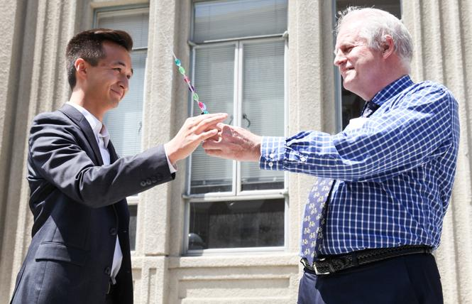 Berkeley City Council candidate Rigel Robinson, left, takes a symbolic baton from longtime City Councilman Kriss Worthington, who is not seeking re-election this year. Photo: Kelly Sullivan