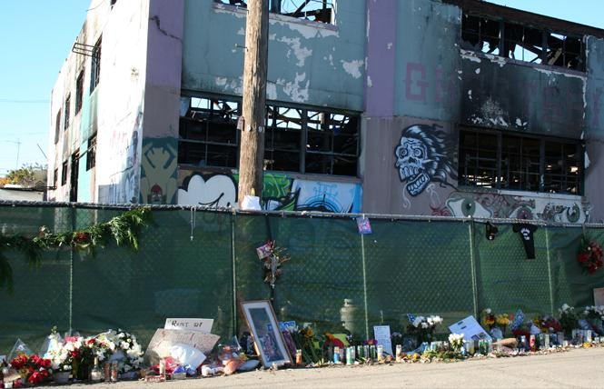 Flowers, candles, and signs line the exterior of the burned out Ghost Ship warehouse a couple of weeks after the 2016 fire that killed 36 people. Photo: Michael Nugent