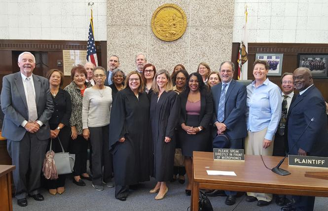 Alameda County Court Commissioner Bentrish Satarzadeh, center left, and Assistant Presiding Judge Tara Desautels, center right, joined other judges and commissioners following Satarzadeh's swearing in. Photo: Cynthia Laird