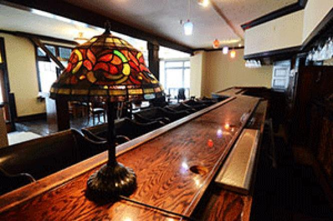 The wooden bar still has its luster at the former Paper Doll Club in North Beach. Photo: Rick Gerharter