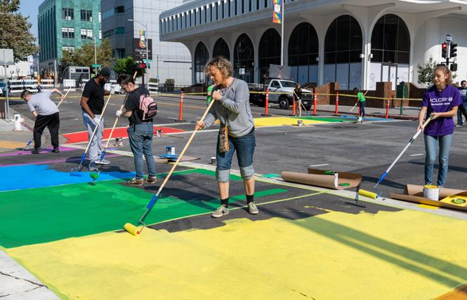 Oakland Pride supporters installed temporary rainbow crosswalks Sunday, September 2, at the site of the festival at 20th and Broadway. From left, Niko Durr, Ari Curry, Rami KD, Lindha Axelssom, and Tia Cutting help paint the crosswalks. Photo: Jane Philomen Cleland