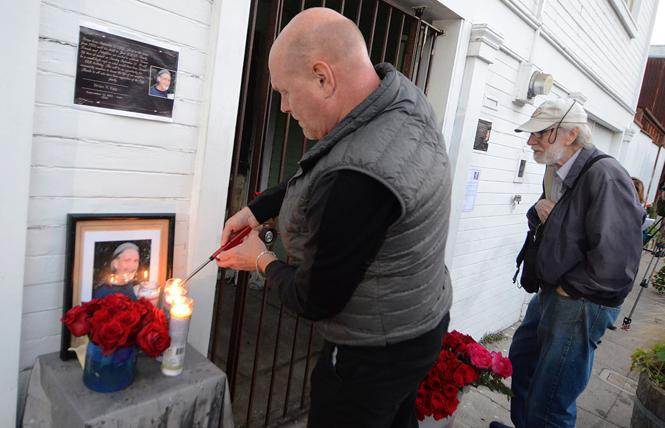 Lee Brandon Espinosa lights a candle in memory of Brian Egg during a vigil outside Egg's home Tuesday, September 11, which would have been Egg's 66th birthday. Photo: Rick Gerharter