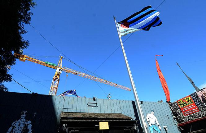 The leather pride flag flies at the Eagle bar as construction continues on a mixed-use development that will pay for a leather-themed public plaza nearby. Photo; Rick Gerharter