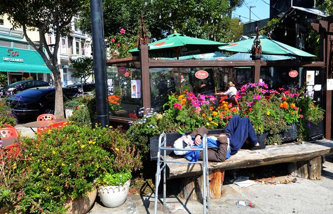 A person sleeps on a bench outside Flore Cafe in San Francisco's Castro district. Photo: Rick Gerharter