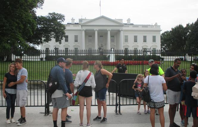 Tourists pose for photos in front of the White House. Photo: Ed Walsh