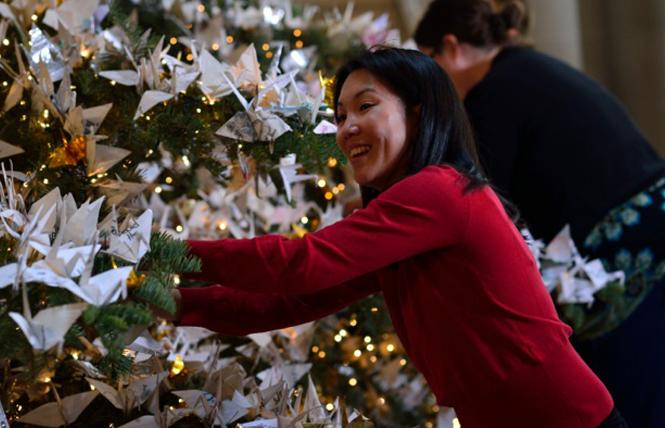 A volunteer helps decorate the World Tree of Hope in 2013. Photo: William Lee