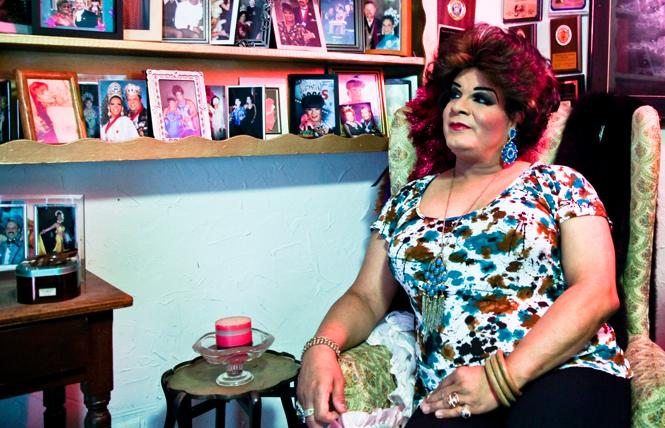 Fredy Miranda, a.k.a. Alexis Miranda, looked at photos that adorn a room in her home, which he will vacate after a legal settlement. Photo: Kelly Sullivan