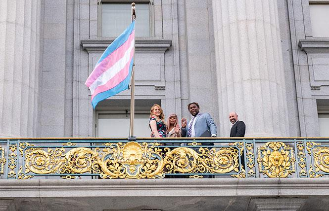 Clair Farley, left, Melanie Ampon, and others wave from the Mayor's balcony at San Francisco City Hall after the transgender flag was raised for the first time Tuesday, November 13. Photo: Jane Philomen Cleland