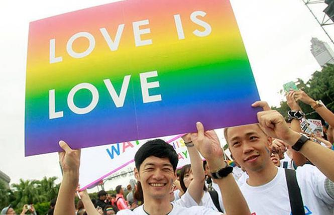 "Two Taiwanese men carry a sign reading ""Love is Love"" following Taiwan's high court ruling to legalize same-sex marriage in May 2017. Photo: Courtesy of Campaign US"