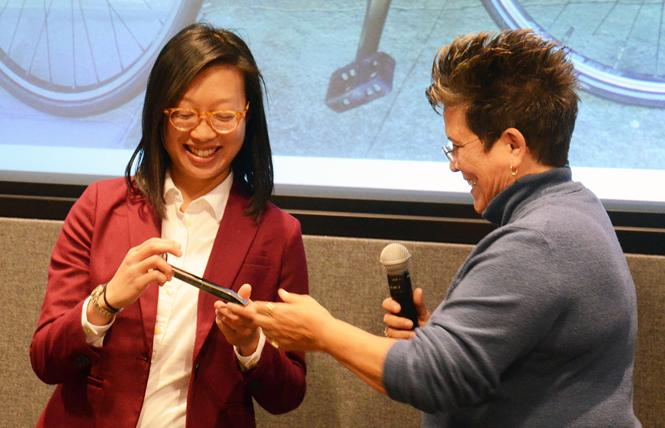 BART director-elect Janice Li, left, smiled as she received a chrome-plated rail spike from BART Assistant Chief Transportation Officer Paula Fraser at a reception Monday. Photo: Rick Gerharter