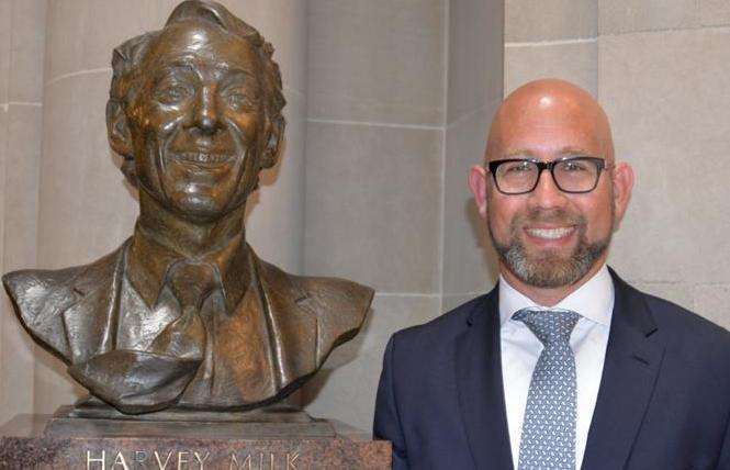Supervisor Rafael Mandelman stands next to the bust of Harvey Milk in City Hall. Photo: Bill Wilson