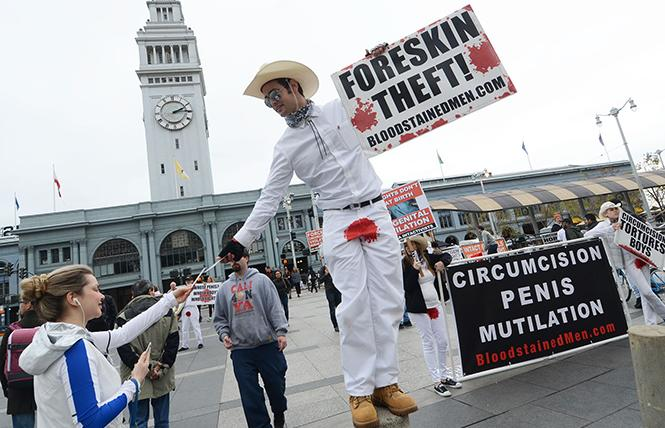 Dominic Barba hands an informational leaflet to a passerby December 15 across from the San Francisco Ferry Building during a demonstration by about 30 activists from Bloodstained Men and Bay Area Intactivists. Photo: Rick Gerharter
