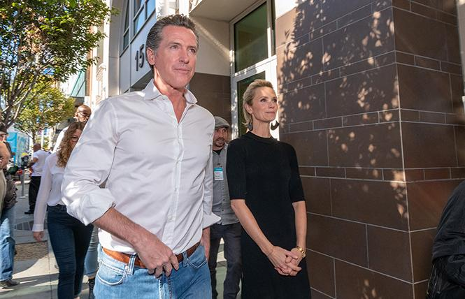 Governor-elect Gavin Newsom and his wife, Jennifer Siebel Newsom, walked to the dining room at St. Anthony's in San Francisco where they helped serve meals shortly after the November election. Photo: Jane Philomen Cleland