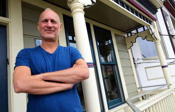 Misterb&b host Alan Lessik stands on the porch of his Victorian cottage in Bernal Heights. Photo: Rick Gerharter