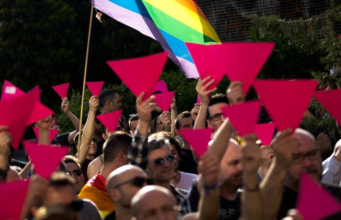 People hold up pink cardboard triangles and wave a rainbow flag during a gathering in support of the LGBT community in Chechnya. Photo: Courtesy U.S. Mission OSCE/Madrid, 2017/AP