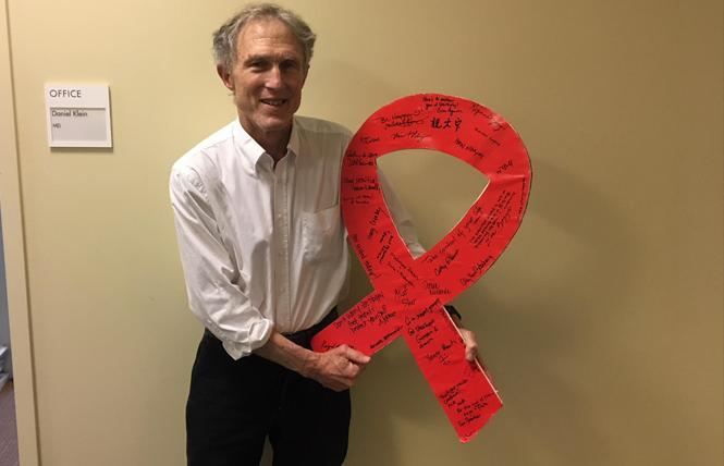 Dr. Daniel Klein holds a red ribbon that includes well wishes from patients and the names of patients lost to AIDS written by Kaiser caregivers. Photo: Courtesy Kaiser Permanente