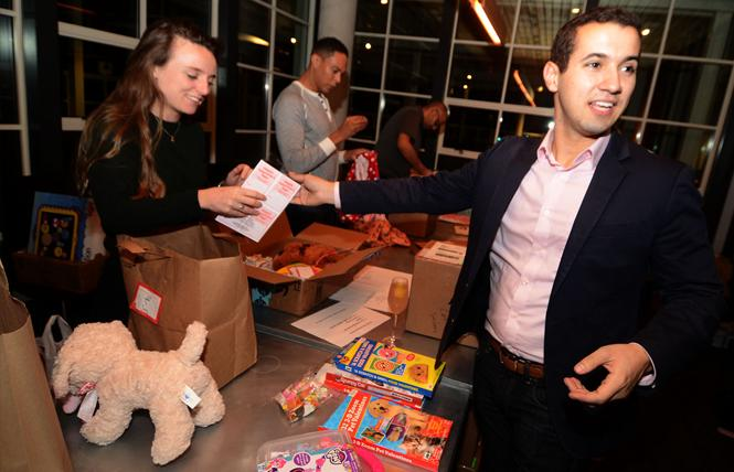 Greg Margida, right, co-founder of the Valentine Project, helped pack gift boxes for distribution to children in the Bay Area at a packaging party January 31. Other volunteers included, from left, Caitlin Keep, Erick Felder, and Amit Lal. Photo: Rick Gerharter