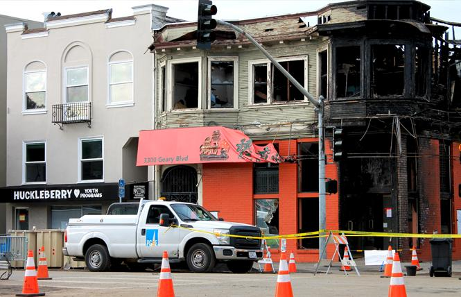 A Pacific Gas & Electric truck sits outside the burned-out Hong Kong Lounge II, right, and Huckleberry Youth Programs, left, which sustained damage during a gas pipe explosion fire February 6. Photo: Heather Cassell