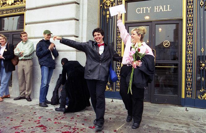 A newly-married couple triumphantly exit San Francisco City Hall following their wedding ceremony on February 15, 2004. Photo: Rick Gerharter