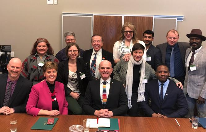 Members of the Dignity Network gathered with Marie-Claude Bibeau, seated, second from left, minister of international development, and Randy Boissonnault, center, special adviser to Prime Minister Justin Trudeau on LGBTQ2 issues, following the announcement of the Canadian government's pledge of $30 million over five years for undeveloped countries. Photo: CNW Group/Rainbow Railroad
