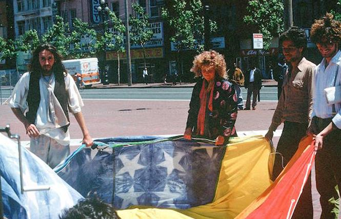 Gilbert Baker, left, and Lynn Segerblom held an original rainbow flag with other volunteers in 1978. Photo: James McNamara, courtesy Paul Langlotz