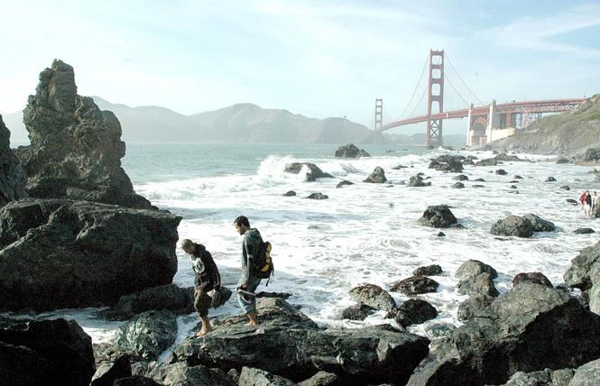 People walk along North Baker Beach, also known as Marshall's Beach, with the Golden Gate Bridge in the background. Photo: Rick Gerharter
