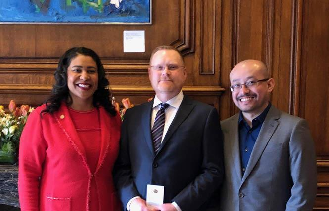 "Mayor London Breed, left, swore in Reese Aaron Isbell March 29 to a seat on the San Francisco Rent Board. With them is Isbell's husband, Sheng ""Bruce"" Yang. Photo: Courtesy SF Mayor's Office"