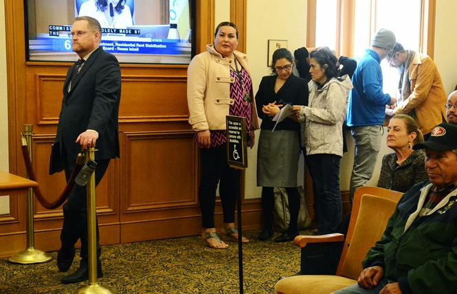 Reese Aaron Isbell, left, stands to the side during a meeting of the Board of Supervisors rules committee Monday as other people wait to speak. Photo: Rick Gerharter