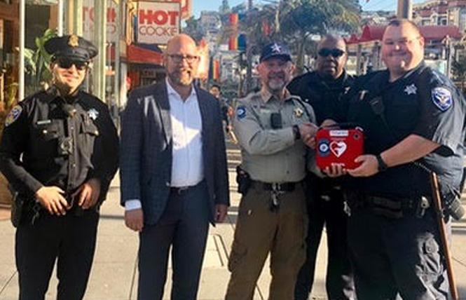 Greg Carey, center, chief of patrol for Castro Community on Patrol, recently handed over an automatic external defibrillator to San Francisco Patrol Special Police Officers TJ Jones and Cody Clements, right. Supervisor Rafael Mandelman, second from left, was joined by a San Francisco police beat officer at the brief ceremony. Photo: Courtesy Greg Carey