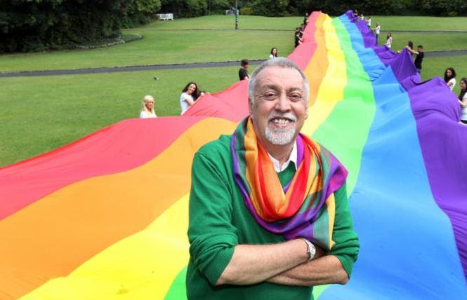 Gilbert Baker stands in front of one his rainbow flags. Photo: Mark Maxwell/courtesy GLBT Historical Society