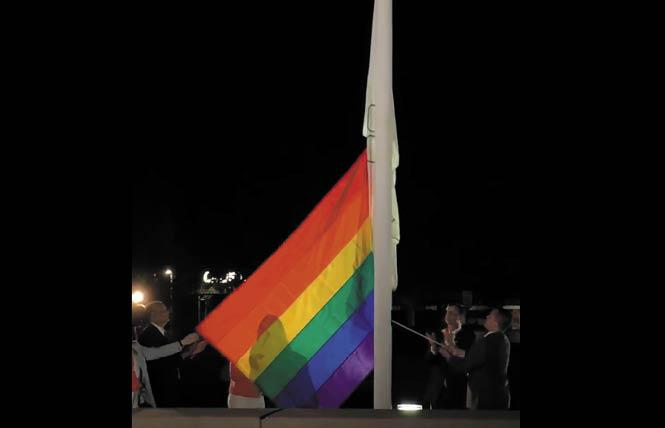 Dublin Mayor David Haubert, second from right, and City Councilman Shawn Kumagai, holding rope, raise the rainbow flag outside City Hall Tuesday Night. Photo: Courtesy Facebook