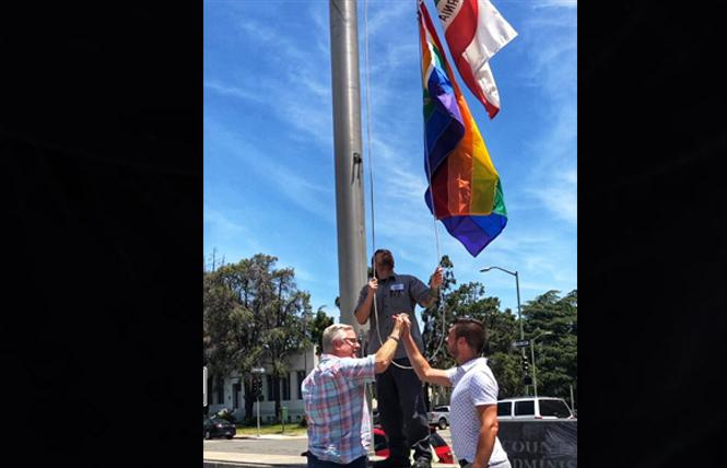 Alameda County Supervisor Scott Haggerty, left, joined Emeryville City Council man John Bauters to raise the rainbow flag at the county office building Tuesday. Photo: Courtesy Twitter