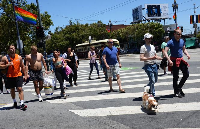 Pedestrians walk on Market Street at Noe, which will be part of the Castro LGBTQ Cultural District. Photo: Rick Gerharter