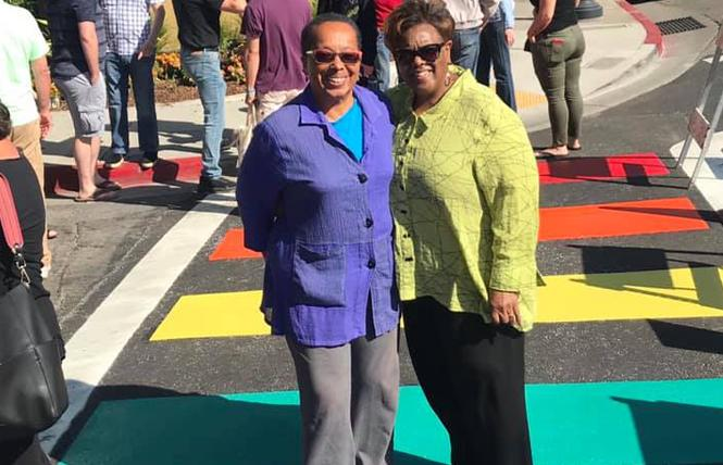 Nancy Hinds, left, and her spouse, Brendalynn Goodall, stand in a rainbow crosswalk that was dedicated last week in San Leandro. Photo: Courtesy Facebook