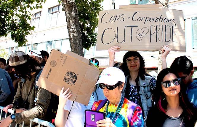 "Sylvia, center, raised their sign ""Cops + Corporations Out of Pride"" along Market Street during Sunday's San Francisco's Pride parade after other protesters halted the event for about an hour. Photo: Heather Cassell"