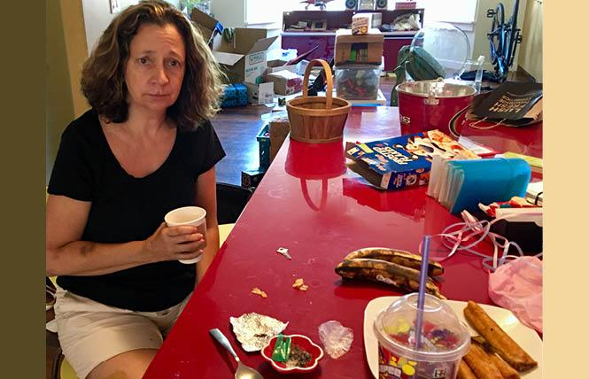 Angela Padilla sits at her dining table where an alleged burglar left drug paraphernalia, foreground, after ransacking and stealing items from her home over the weekend. Photo: Sari Staver